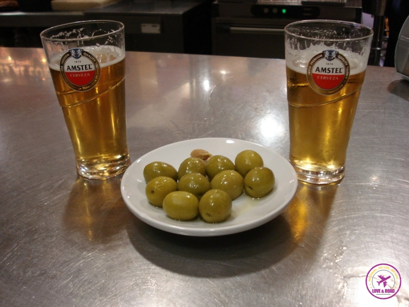 Two glasses of beer and a plate of green olives.