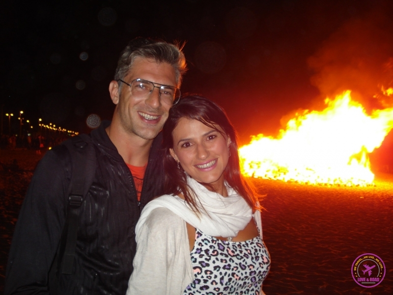 Couple smiling in front of bonfire.