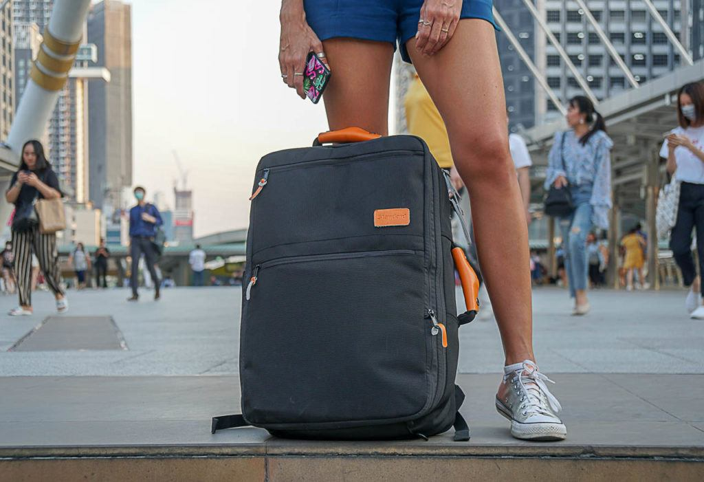 A woman standing in a busy station using the Standard Luggage suggested as a good travel gift.