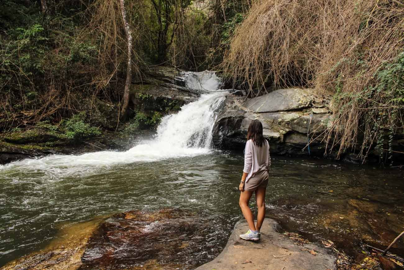A woman looking at waterfall and trying new things to do in Chiang Mai goes on an expedition to the Chiang Mai mountains.