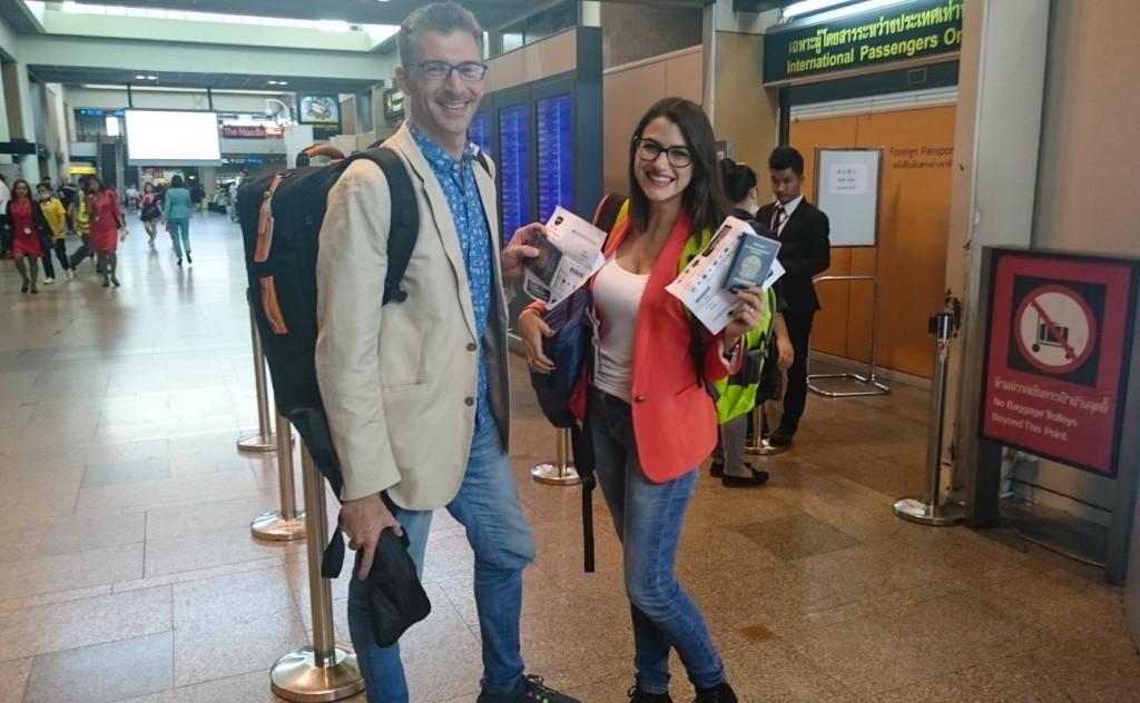 Casal posando em um aeroporto com os documentos de embarque nas mãos. Eles estão felizes porque receberam vouchers de indenização por overbooking.