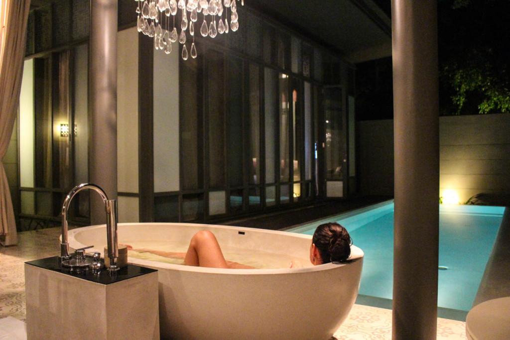 Woman taking a bath in luxurious Thailand Honeymoon at SALA Phuket villa.