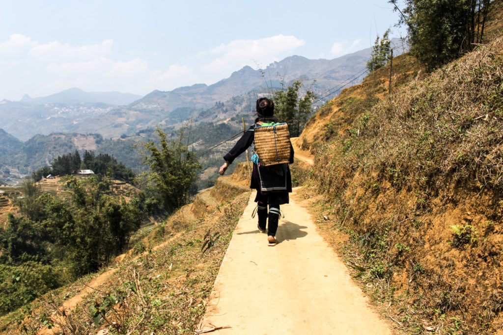 Woman walking on a trail through the rice terraces in Sapa Mountains, Vietnam. This is one of the must-see places in Vietnam.