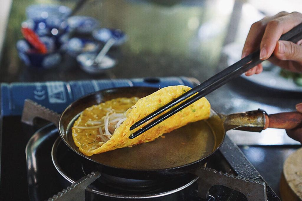 A Vietnamese rice pancake being cooked in an Iron flat pan. It's of the many traditional food Vietnam is famous for.