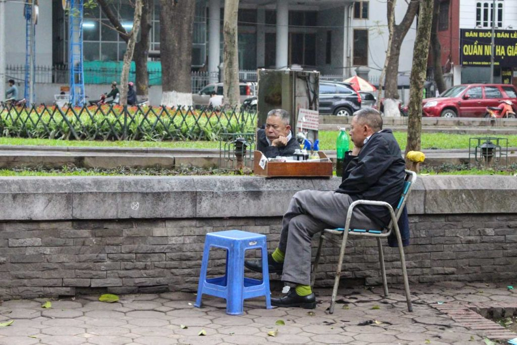 A street barber waiting for customers. This a local scene you can spot while search of things to do in Hanoi.