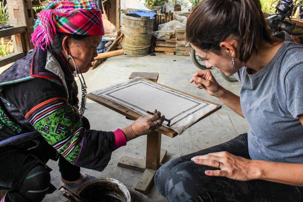 Traveler learning how to painting with a local woman from Sapa Mountains in Vietnam.
