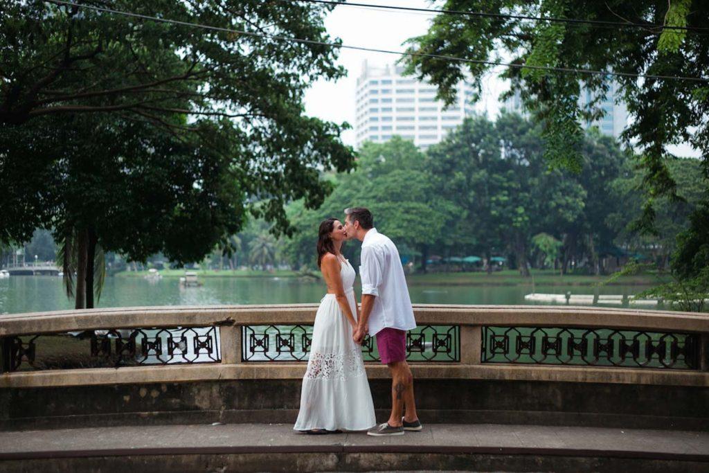Casal dando um beijo de mãos dadas no parque Lumpini, em Bangkok.