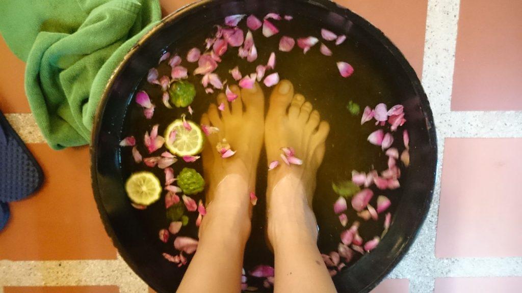 Pés recebendo momentos de relaxamento em spa de Bangkok.