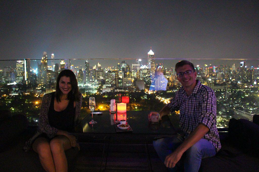 Casal aproveitando uma noite romântica em um bar na cobertura em Bangkok.