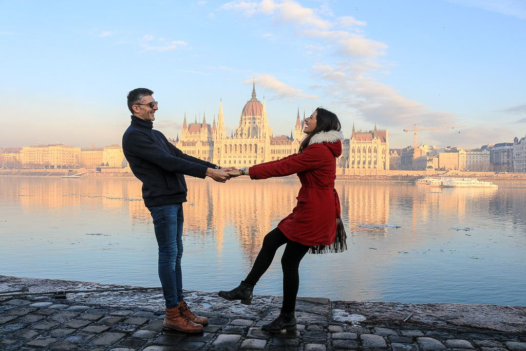 A couple laughing in front of the Budapest parliament, one of the most iconic buildings in Central Europe. Budapest is a destination you must add to your 2-week Europe itinerary.