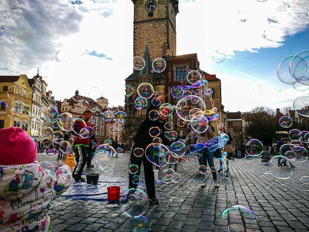 Homem soltando bolhas de sabão nas ruas de Praga.