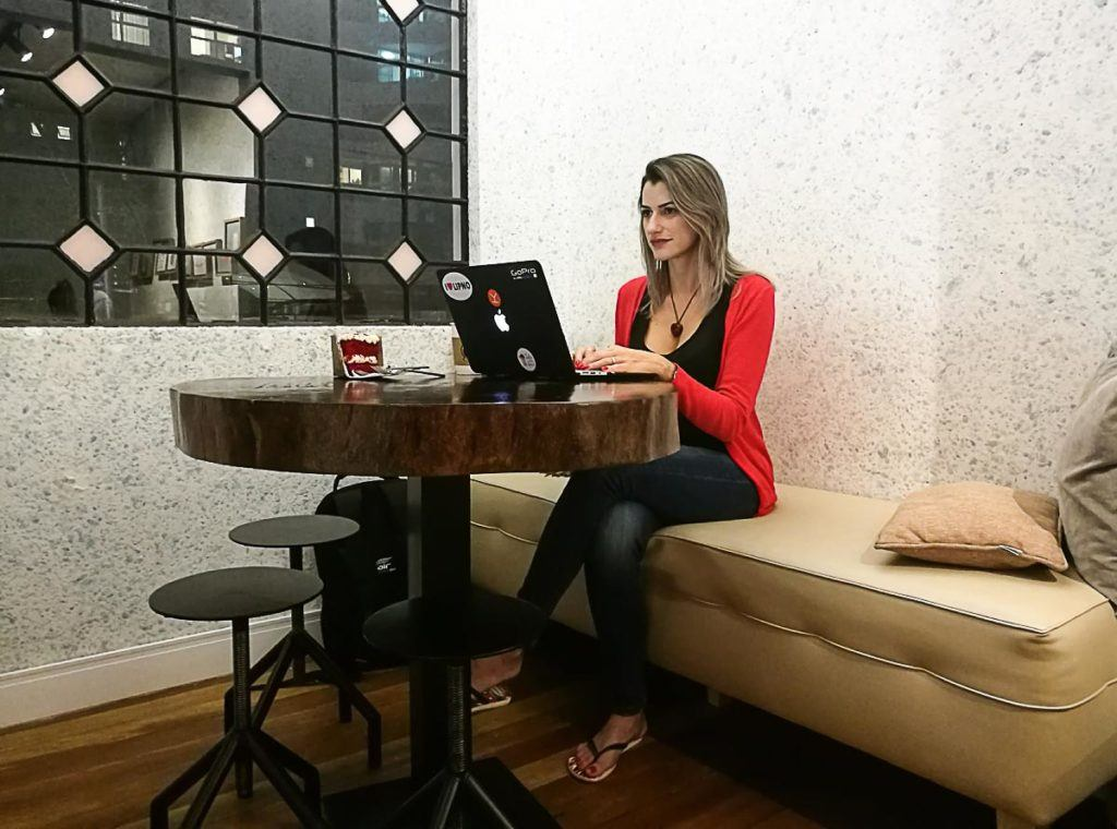 Woman in a cafe working from a laptop while she travels the world.