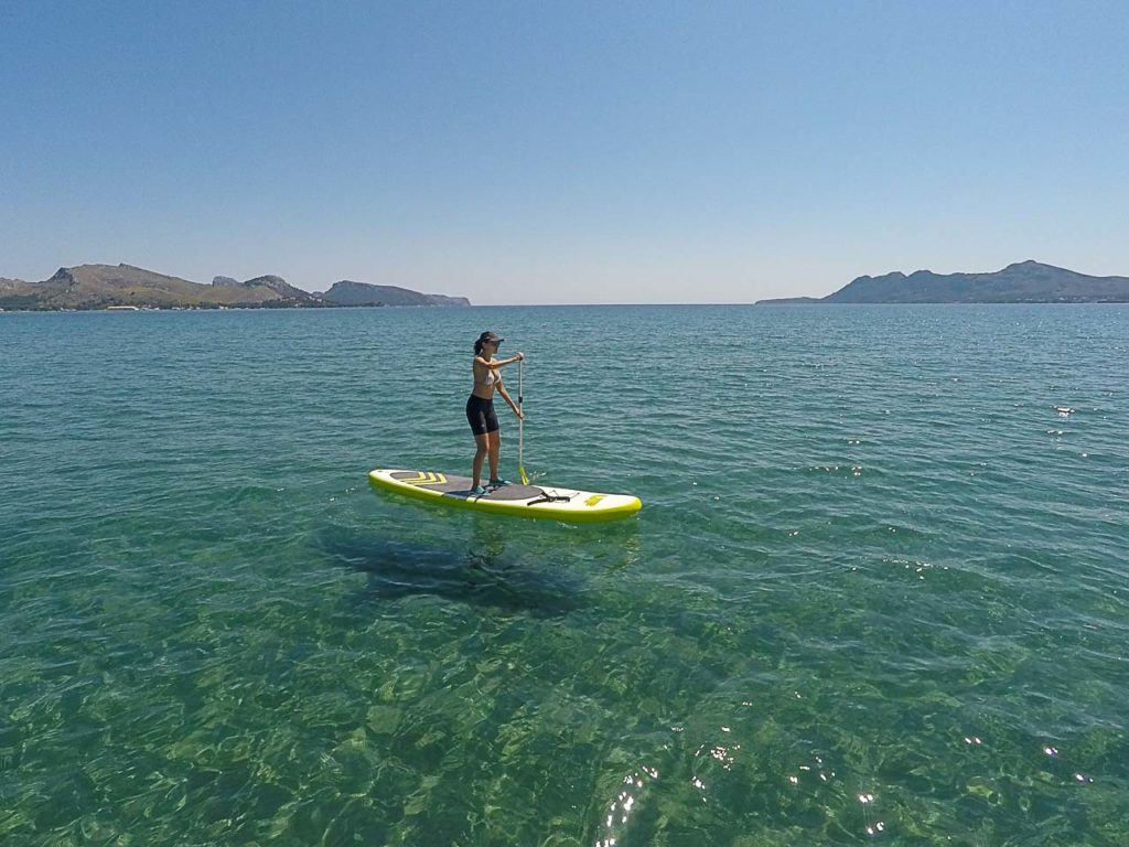Woman stand up paddling through the ocean in a bootcamp in Spain.