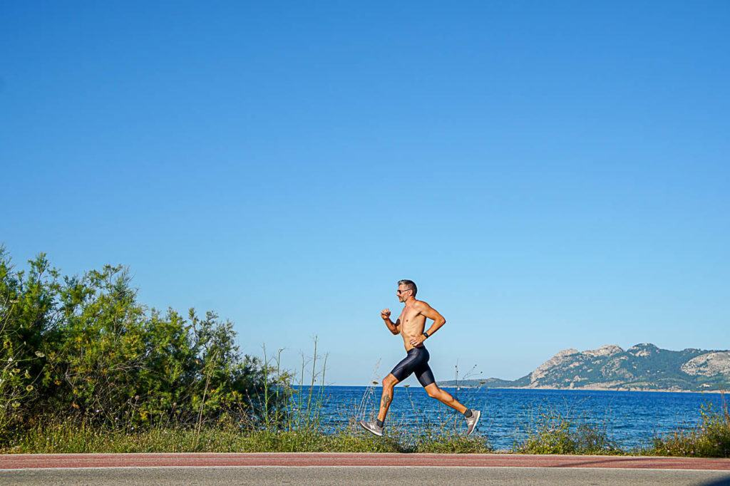 Man running along the ocean in bootcamp in Spain.