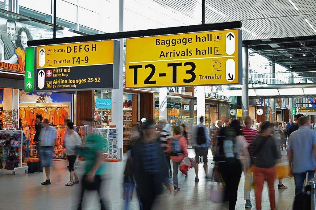 Pessoas caminhando em um aeroporto cheio de gente.