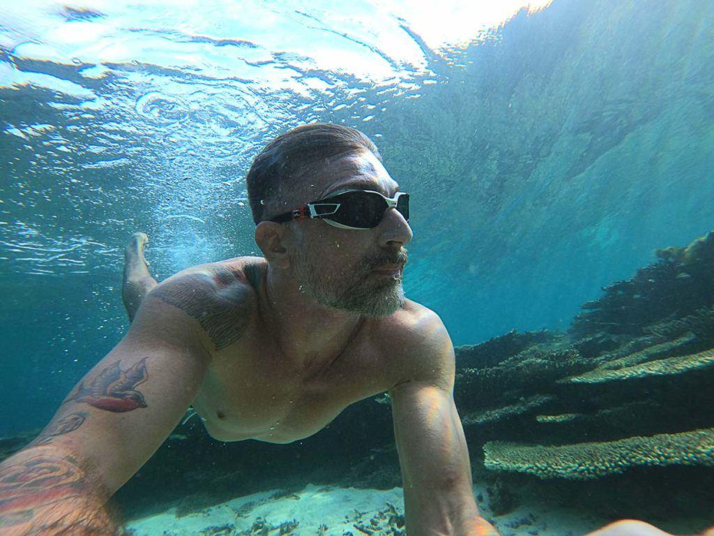 Homem nadando em água cristalina das Ilhas Maurício.
