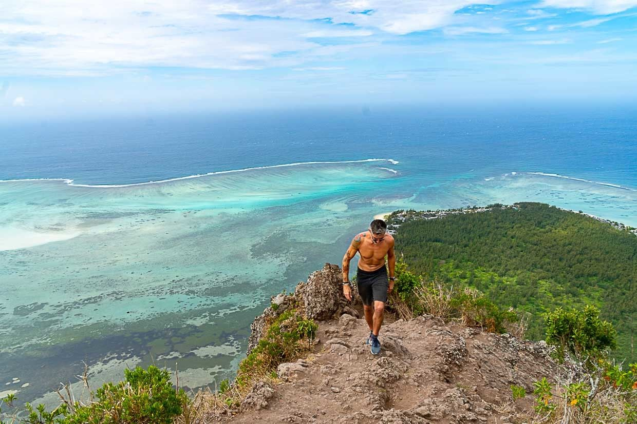 Man hiking up a hill in Mauritius. He learned how to save money while traveling.
