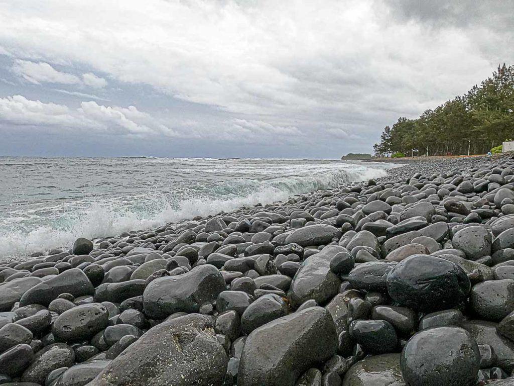 The Riviere des Galets Beach is unique with its black pebbles stones.