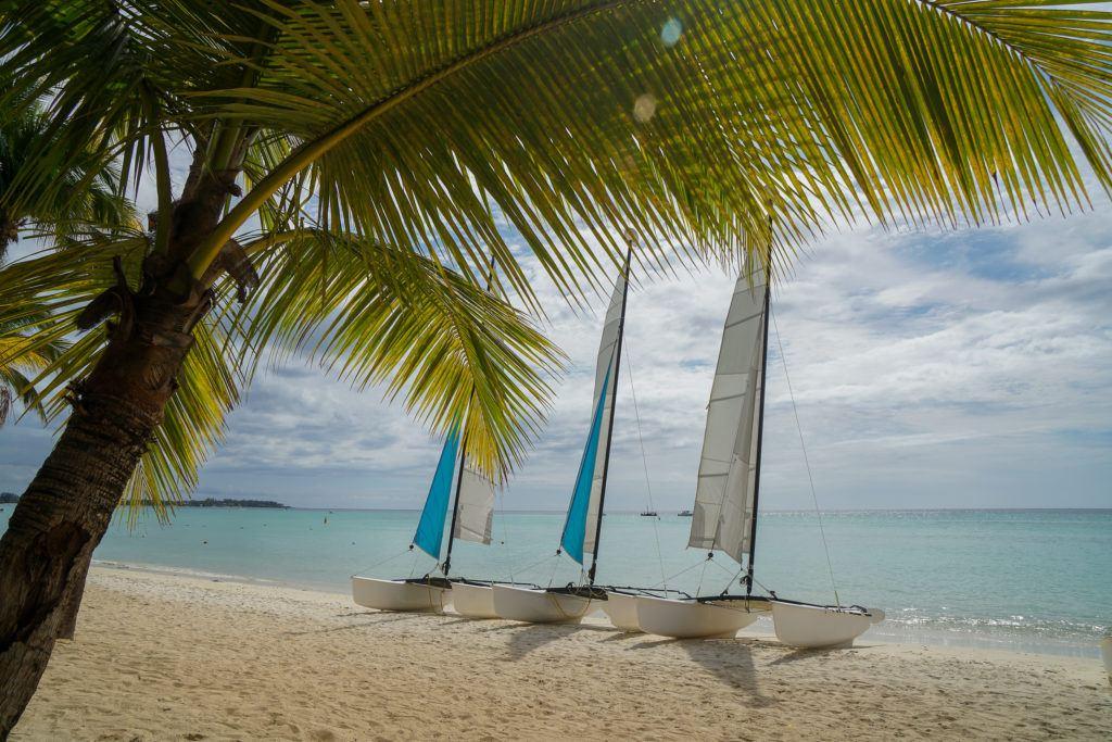 Foto na praia das Ilhas Maurício com três pequenos catamarãs na areia.