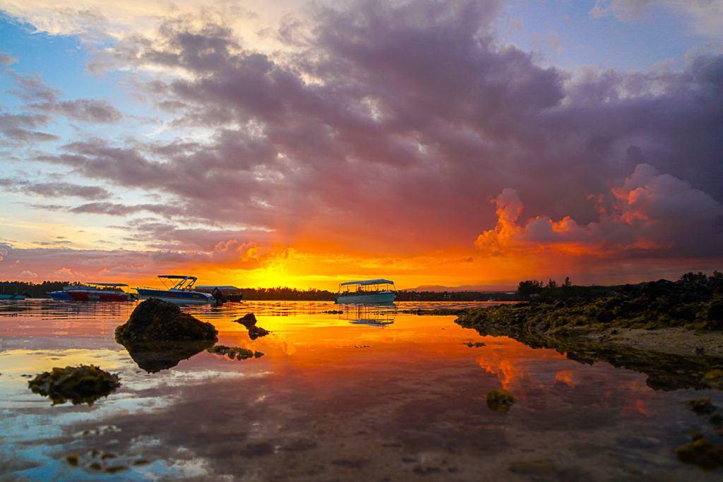 Pôr do sol em uma praia nas Ilhas Maurício, com o reflexo do sol na água.