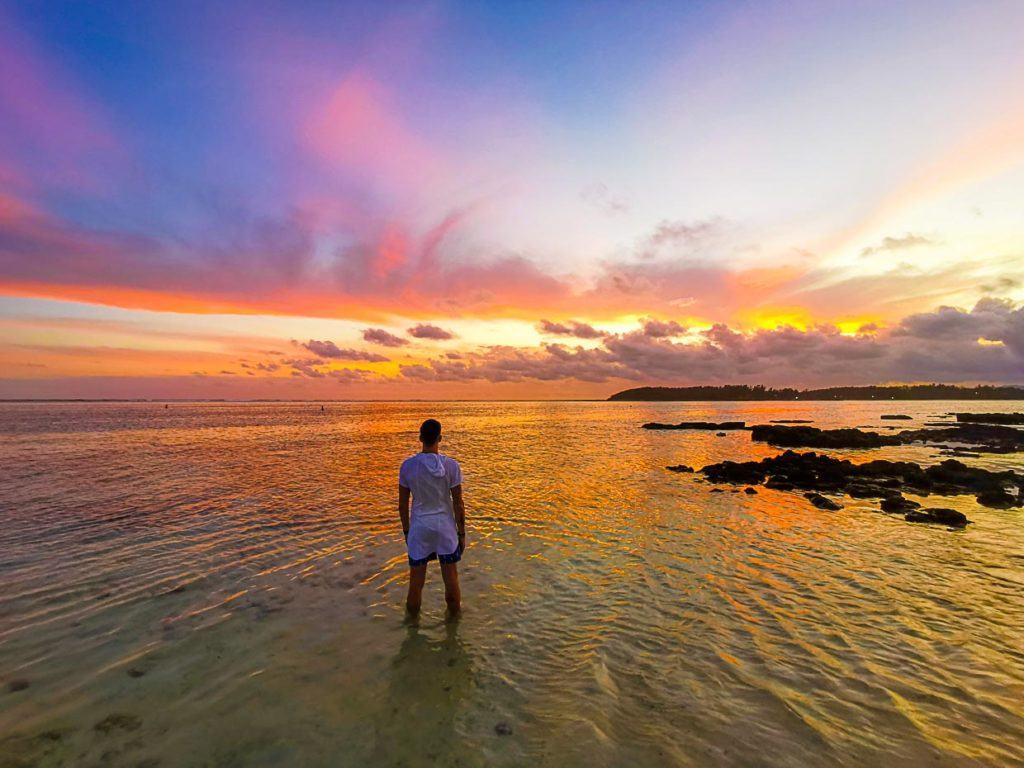 Foto de pôr do sol incrível nas Ilhas Maurício, com céu amarelo e nuvens fofas e coloridas.