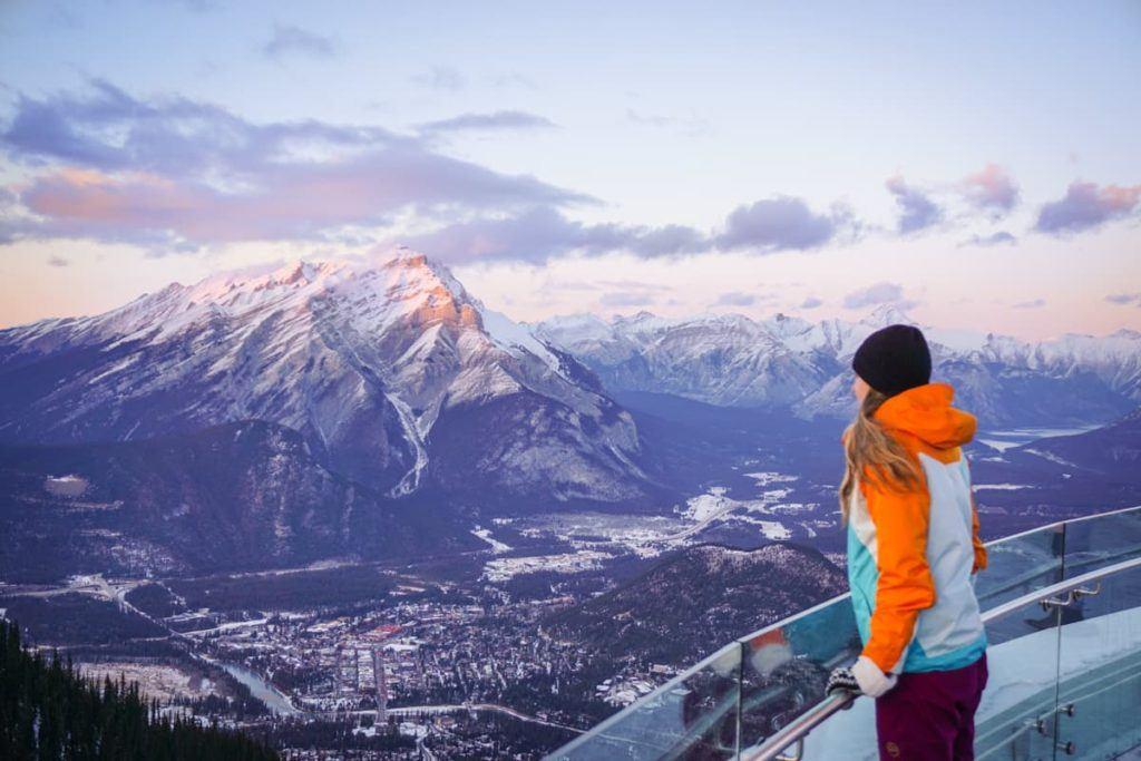 Viajante em um mirante admirando as Montanhas Rochosas Canadenses com seus picos nevados.