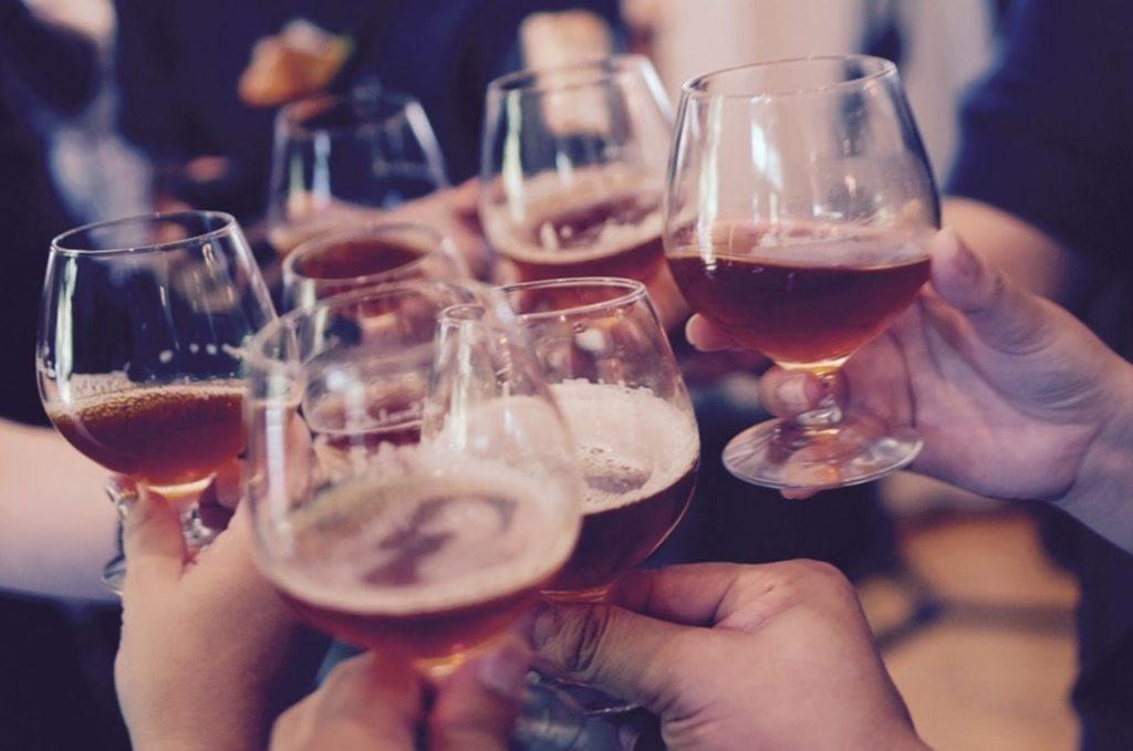 Pessoas celebrando com copos cheios em uma das melhores cervejarias de Nova York.