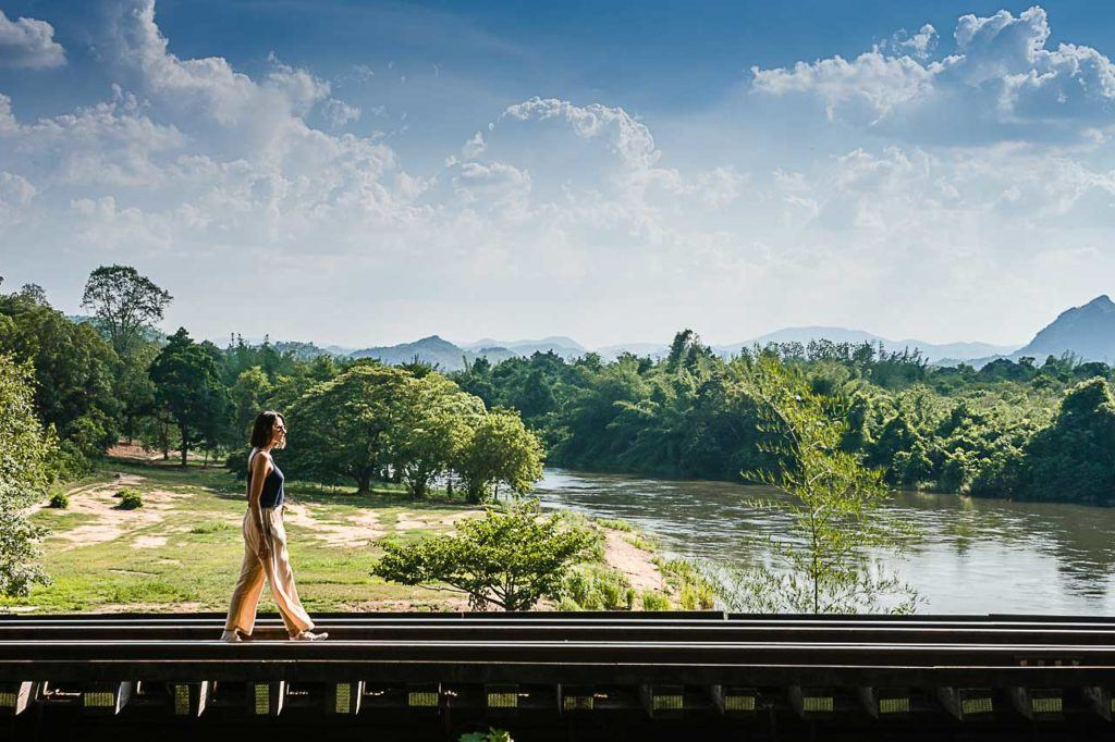 A traveler is walking over the track of the Death Railway also known as the Thailand - Burma Railway.