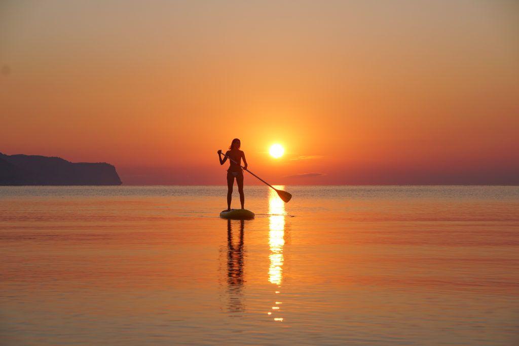 Mulher fazendo stand up paddle no nascer do sol de Porto de Pollensa.
