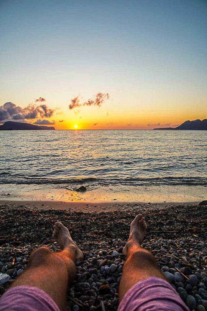 Pernas de homem vendo nascer do sol em Porto de Pollensa.