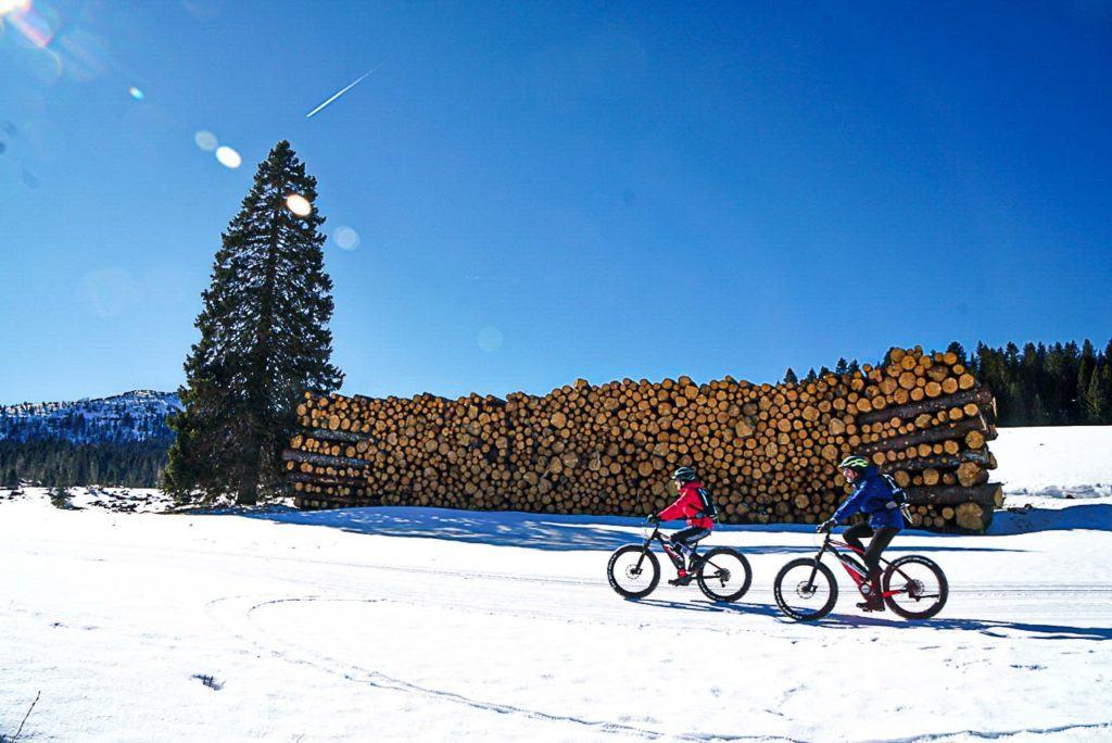 Traveler couple riding bicycles at Folgaria Lavarone ski area, in Alpe Cimbra.