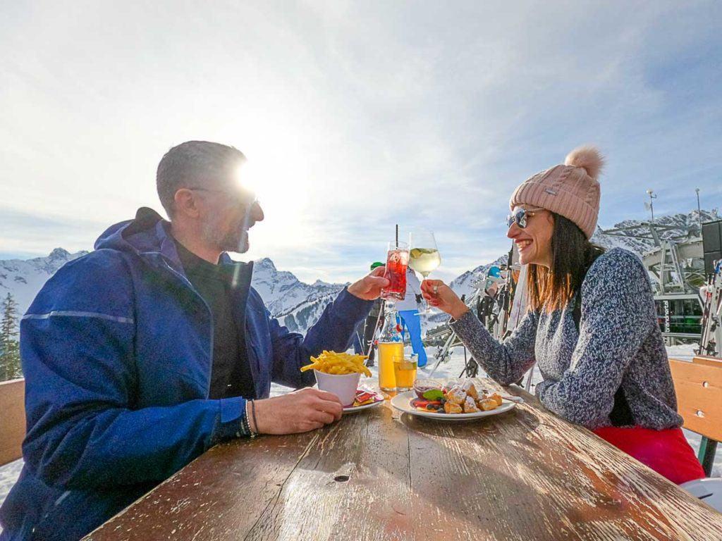 Casal de esqui fazendo um brinde no Restaurante Frööd, em Brandnertal.