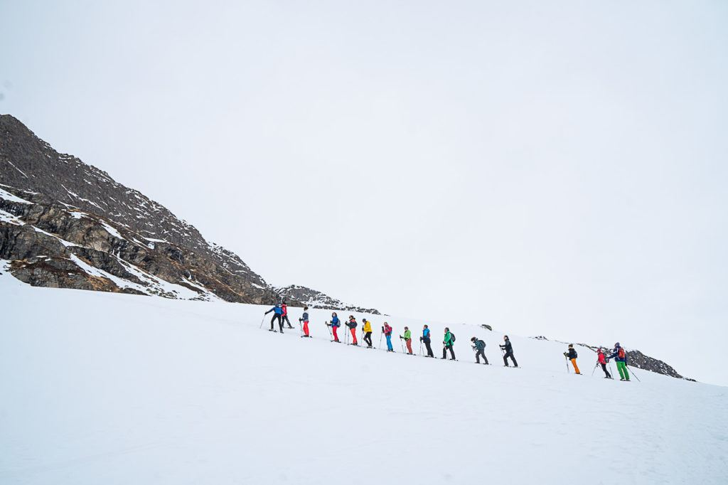 People lined on snowshoe hike to Silvrettassee Mountain Lake.