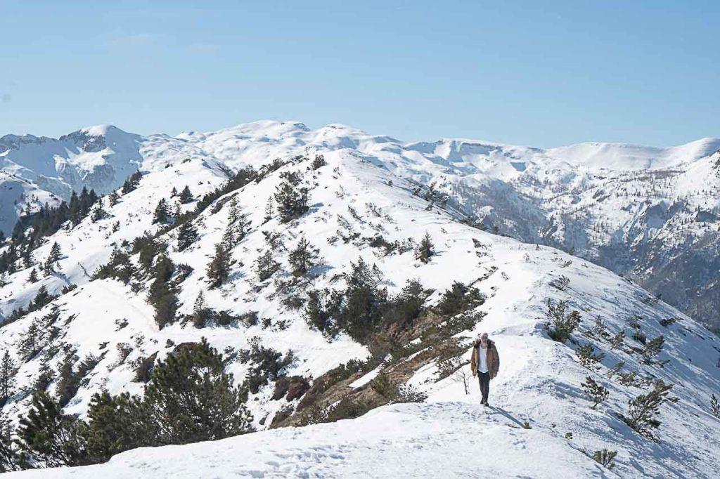 Man walking alone on snowy mountains at Folgaria Lavarone ski area.