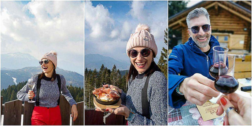 Love and Road couple enjoying wine and food at Rifugio Baita del Neff, in the Lavarone Ski Area.