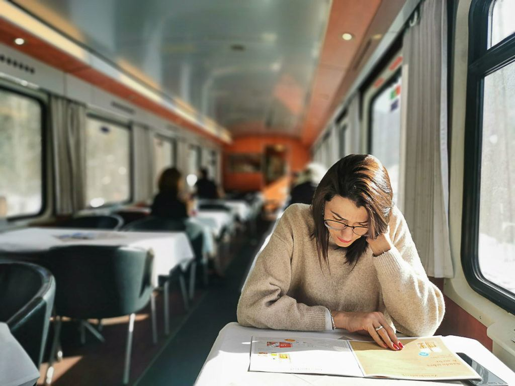 Mulher lendo no trem, que é uma boa opção para viajar para Brandnertal.