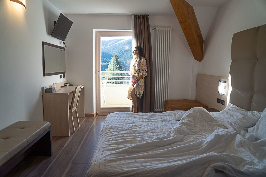 Woman looking outside by the balcony at Hotel Vittoria, located in Folgaria ski area in Alpe Cimbra, Italy.