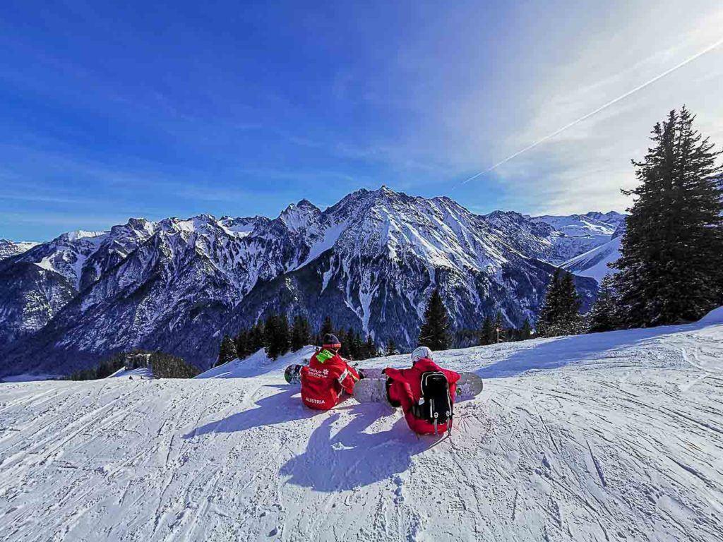 Duas pessoas praticando snowboard e esqui em Brandnertal.