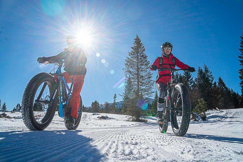 Couple riding fat bikes at Passo Coe, in the Folgaria Ski Area in Alpe Cimbra.