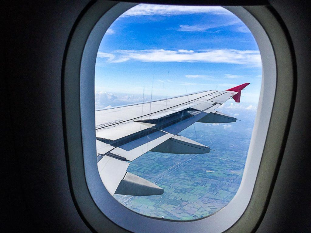 Airplane window showing the plane's wing and a blue sky.