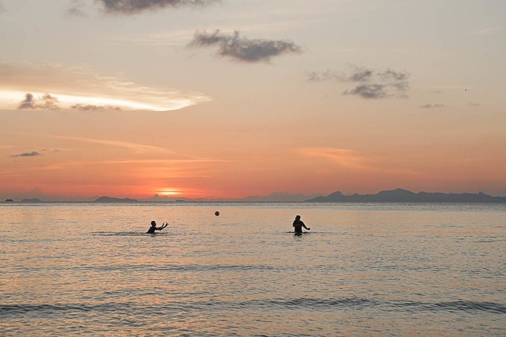 Kids playing ball on the ocean of Thailand.