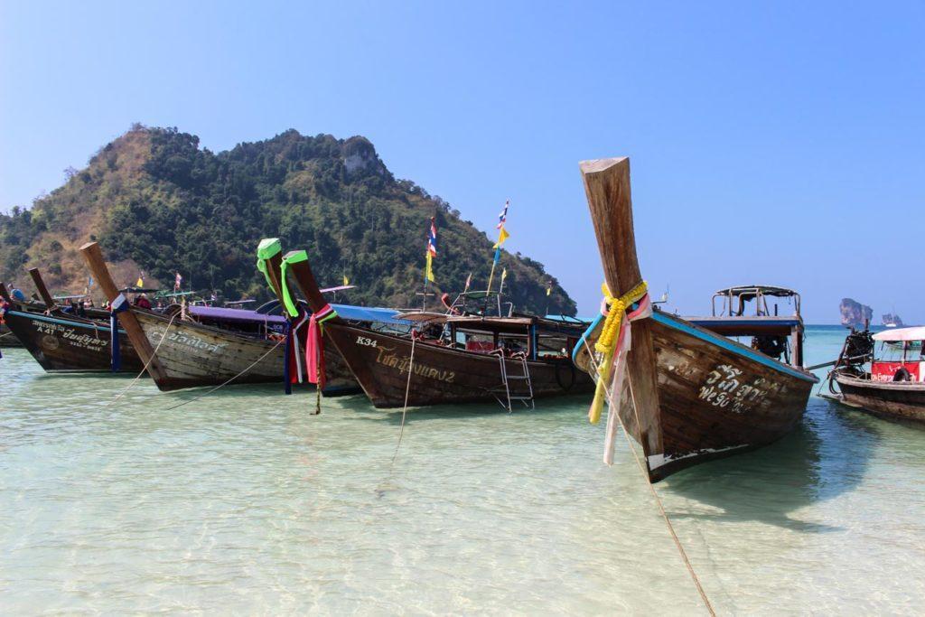 Barcos tailandeses sobre um mar de águas cristalinas. Descubra como chegar em Krabi, um destino deslumbrante localizado na costa sudoeste da Tailândia.