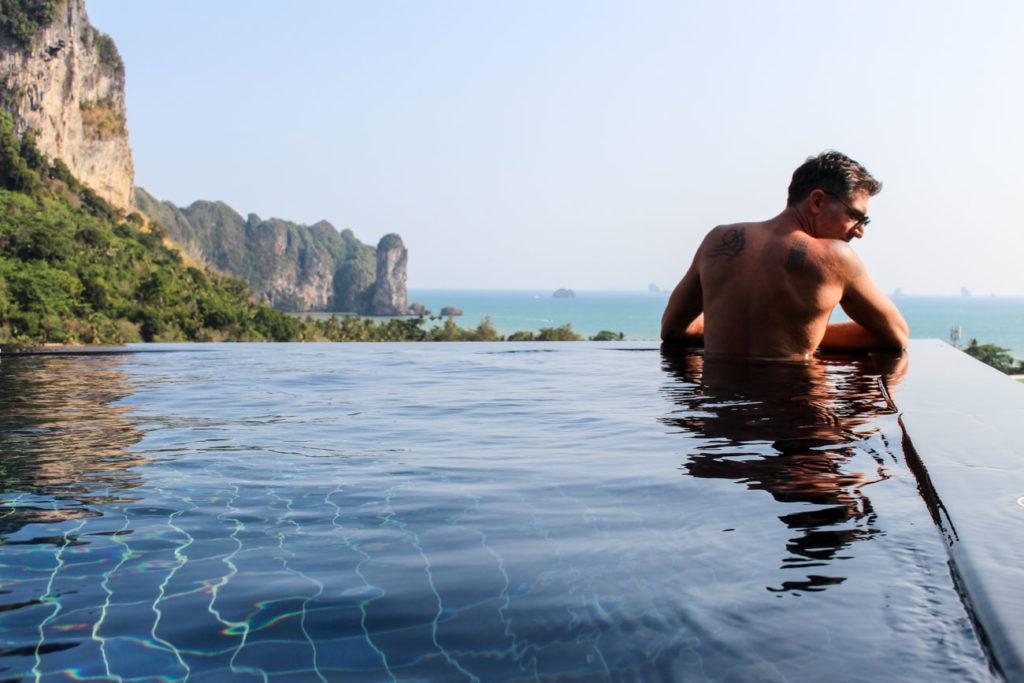 Homem relaxando em uma piscina infinita na Tailândia. Ele é fotógrafo e um dos blogueiros do Love and Road.