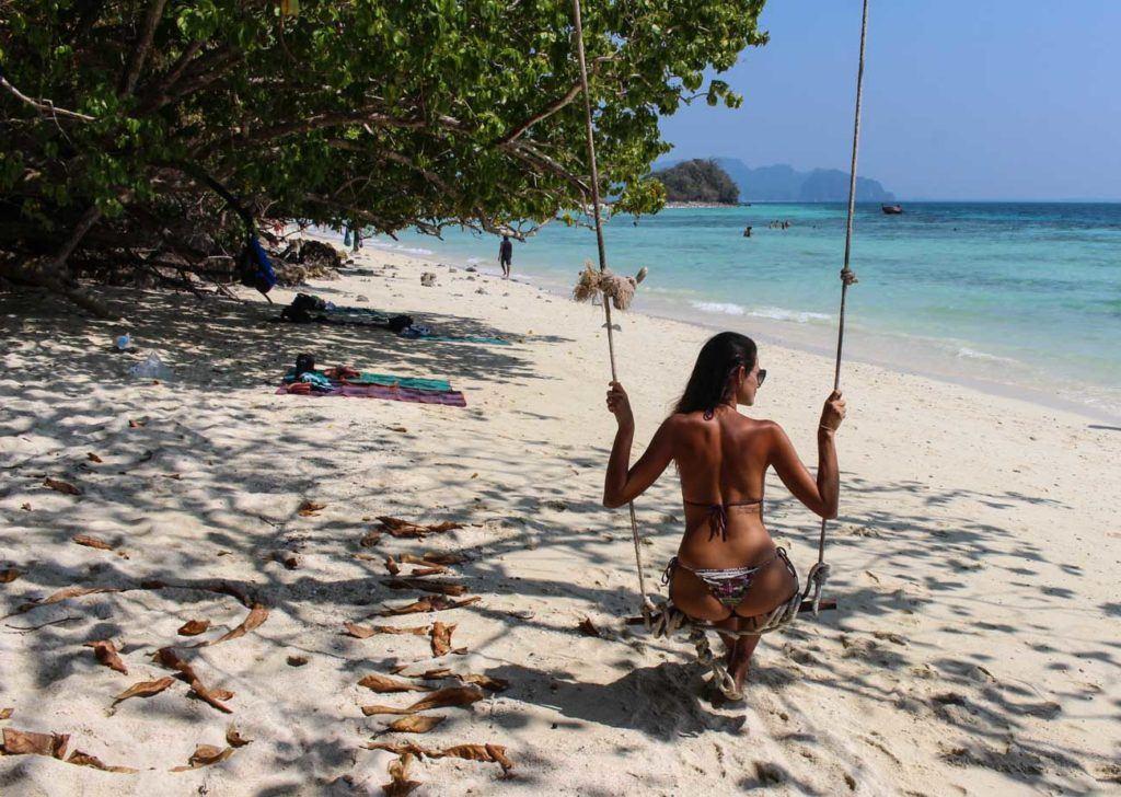 Mulher no balanço em uma praia da Tailândia. Natalie (ou apenas Nat) escreveu este artigo sobre como ir para Krabi.