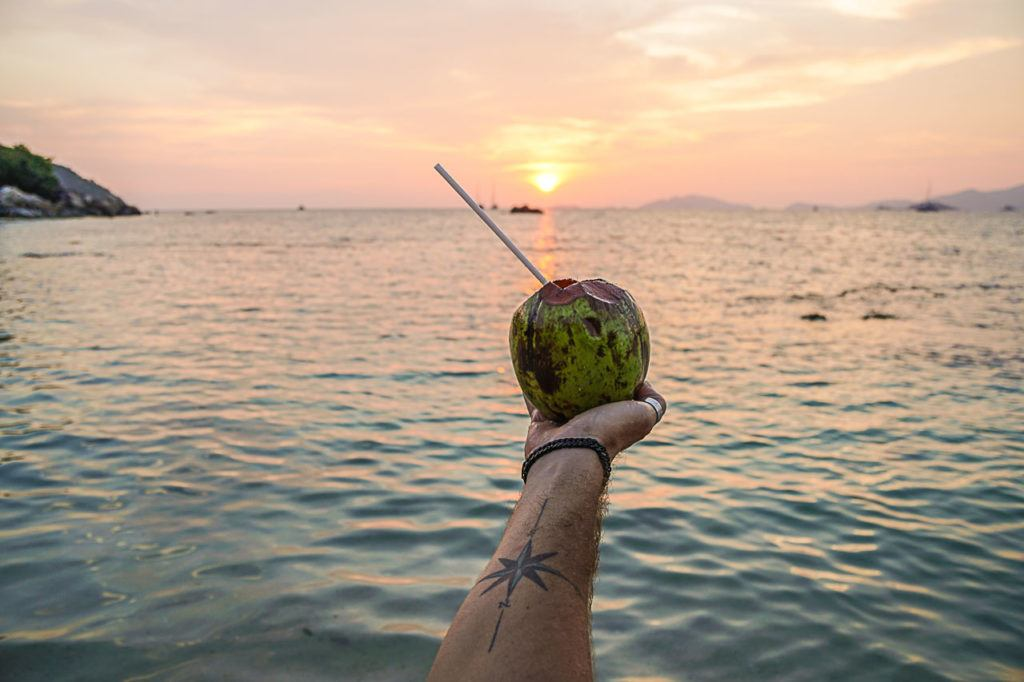 Coconut being held upon the sea of Thailand.
