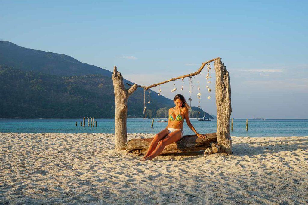 Woman sunbathing on a Sunrise beach in Koh Lipe, Thailand.