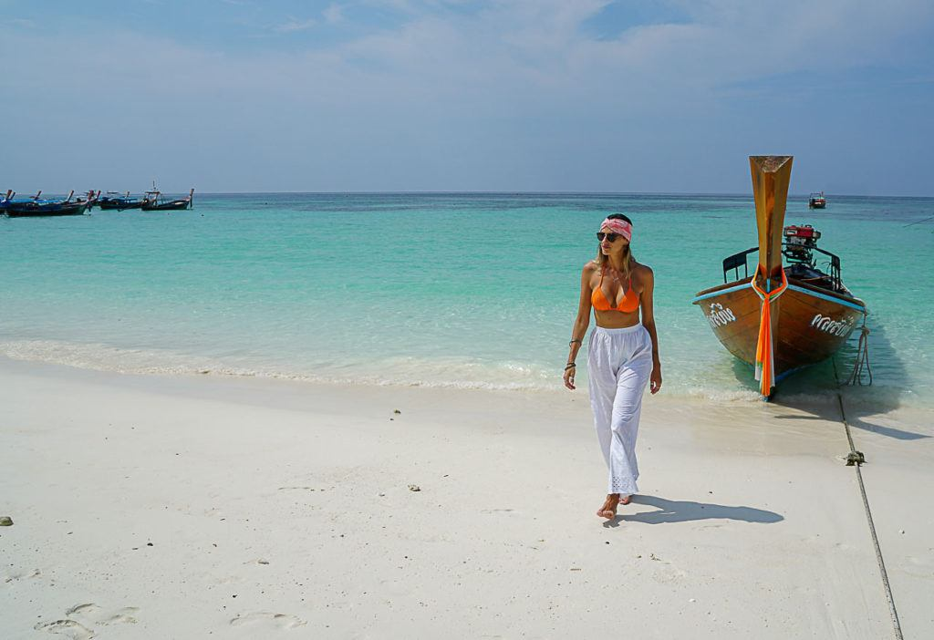 Woman on the beach in Thailand with white sand and turquoise water.
