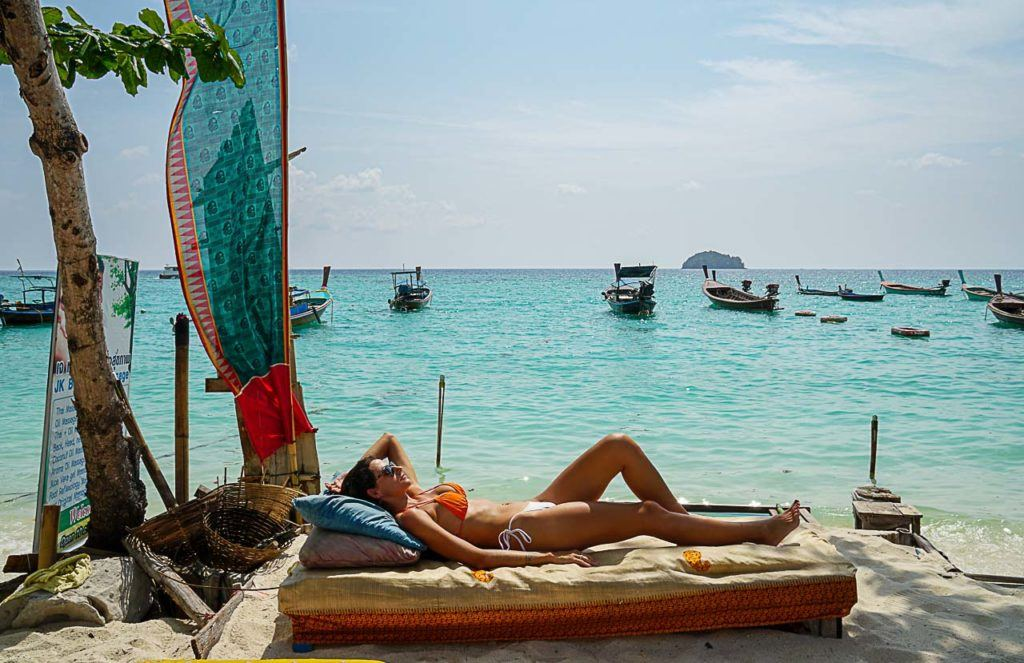 Woman sunbathing in Sunrise Beach, one of the best places to stay in Koh Lipe.