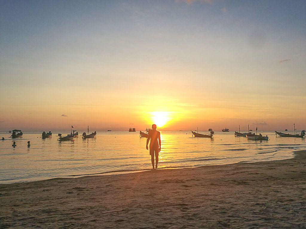 Homem de pé na Sairee Beach admirando o mar e o sol.