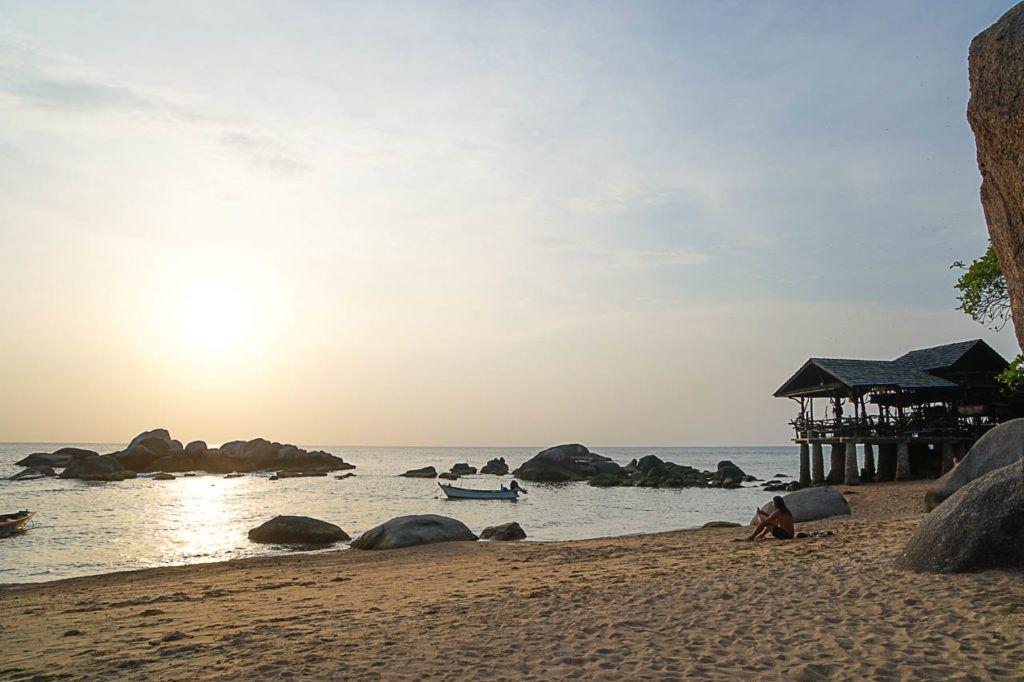 Um homem e um barco na praia de Koh Tao.